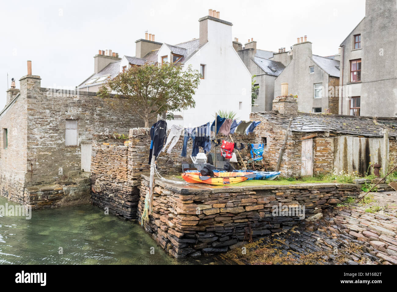 sea kayaks and wetsuits drying on washing line in seafront garden in Stromness, Orkney, Scotland, UK - Stock Image