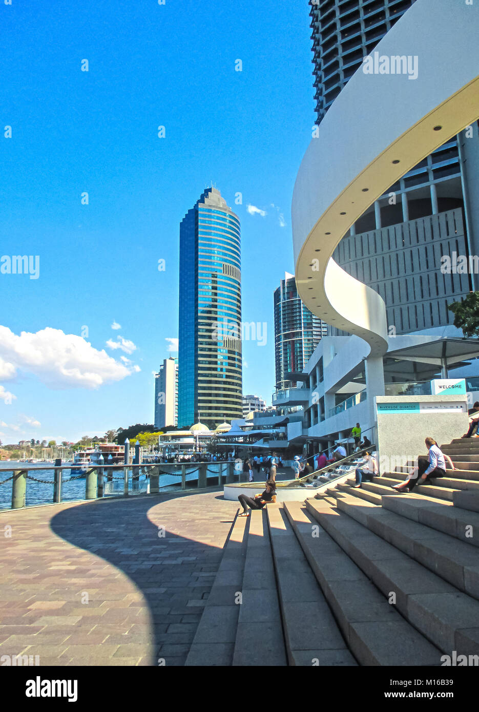 People sitting on the steps near the Eagle Street Pier with sky scrapers in the background in the CBD Brisbane Queensland - Stock Image