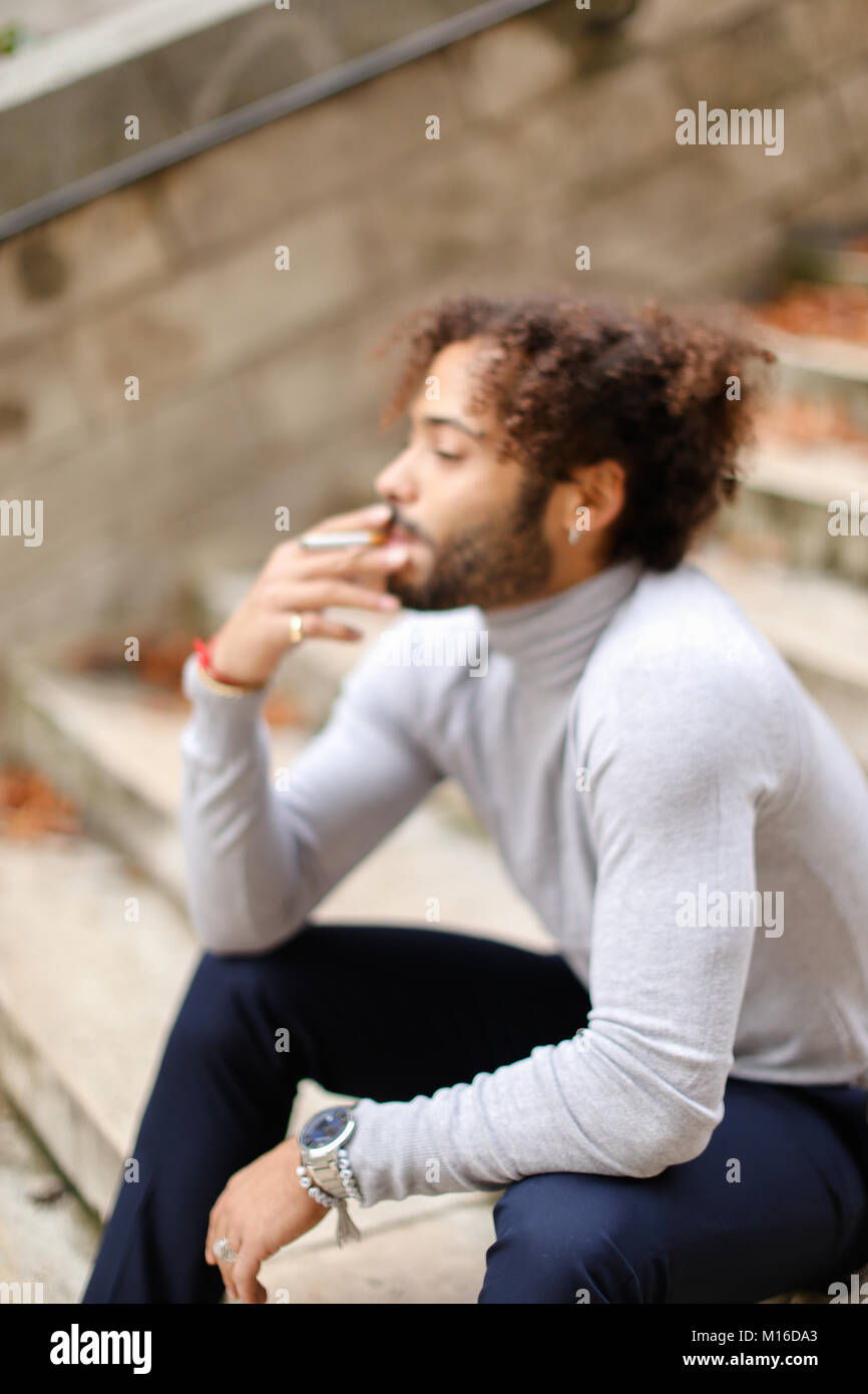 Young smoker coughing on steps with cigarette. - Stock Image
