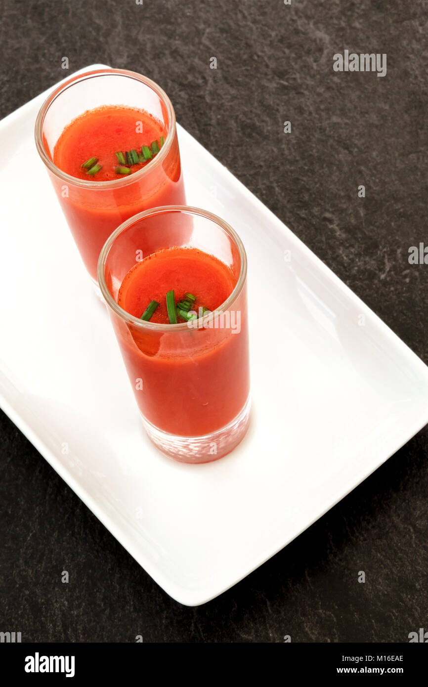 Spanish tapas in a modern bar. Two shots of gazpacho, cold tomato soup, on a dark black table with a place for text - Stock Image