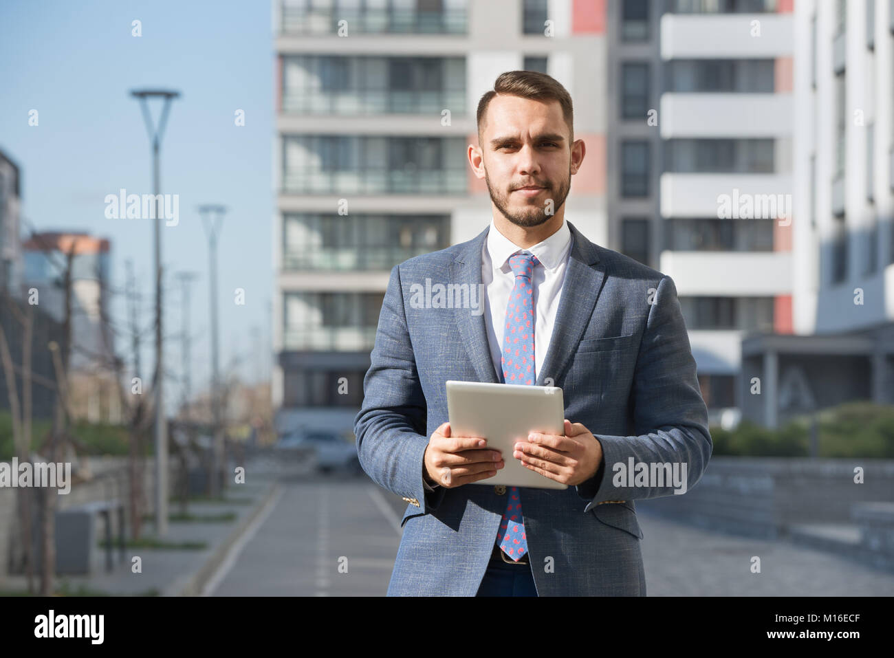 Businessman or real estate agent with tablet computer against new building - Stock Image