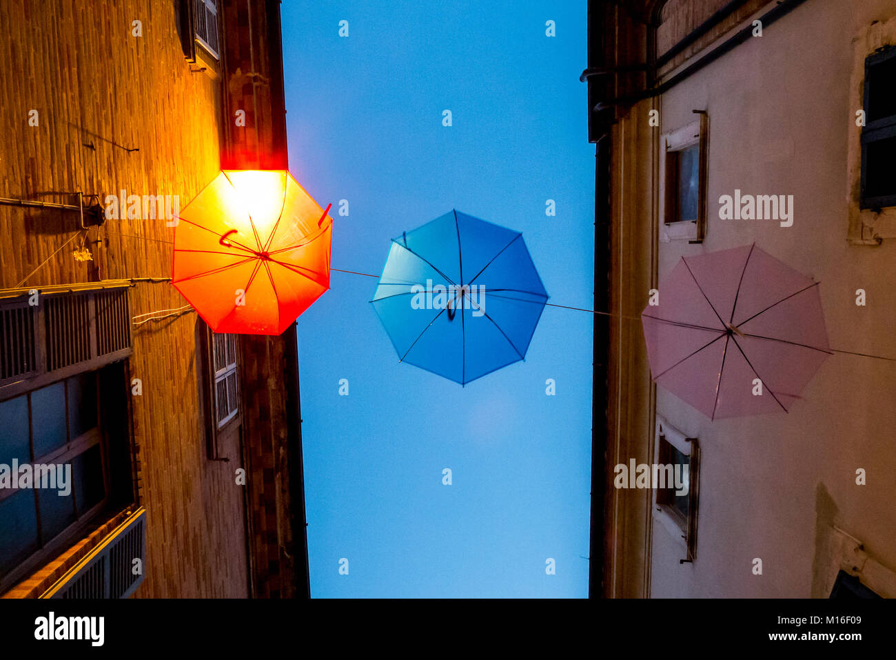 Colorful umbrellas hanging and swinging in an urban alley - Stock Image