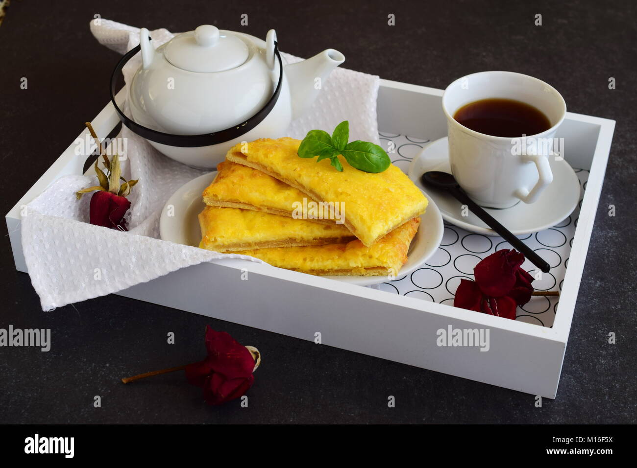 cheesy pancakes with tea on a wooden tray. ideas for breakfast stock