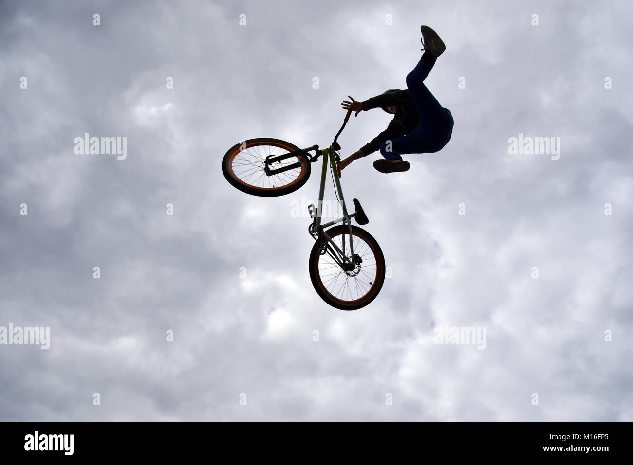 Silhouette of a young man freestyle stunt cyclist flying in the sky performing stunt jump from a skatepark ramp Stock Photo