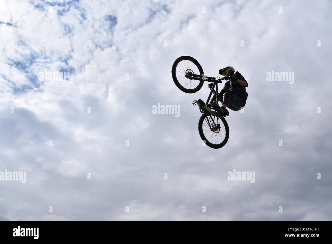 Silhouette of a young man freestyle stunt cyclist flying in the sky performing stunt jump from a skatepark ramp - Stock Image