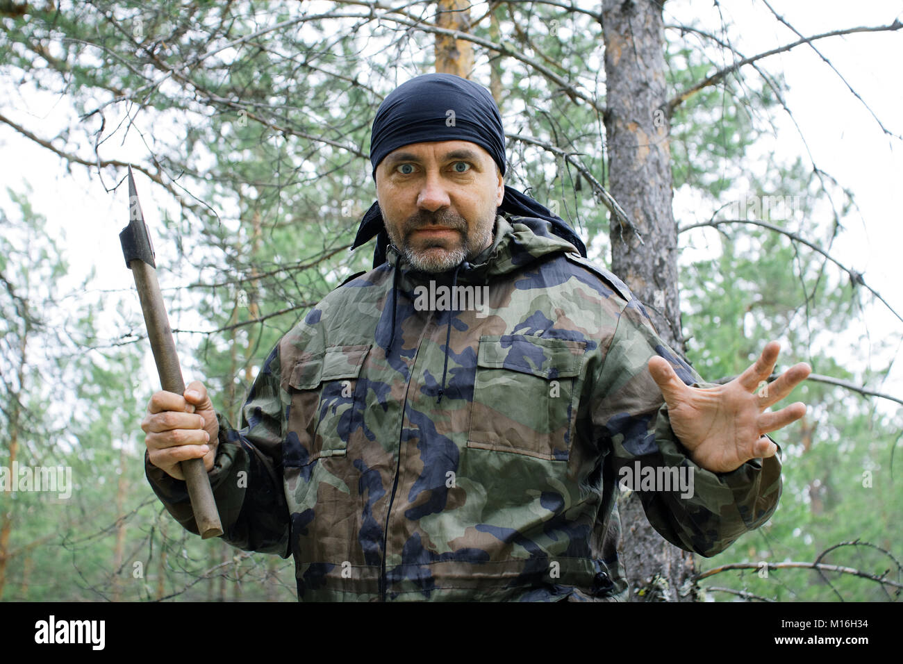 Furious man with an ax in the taiga - Stock Image