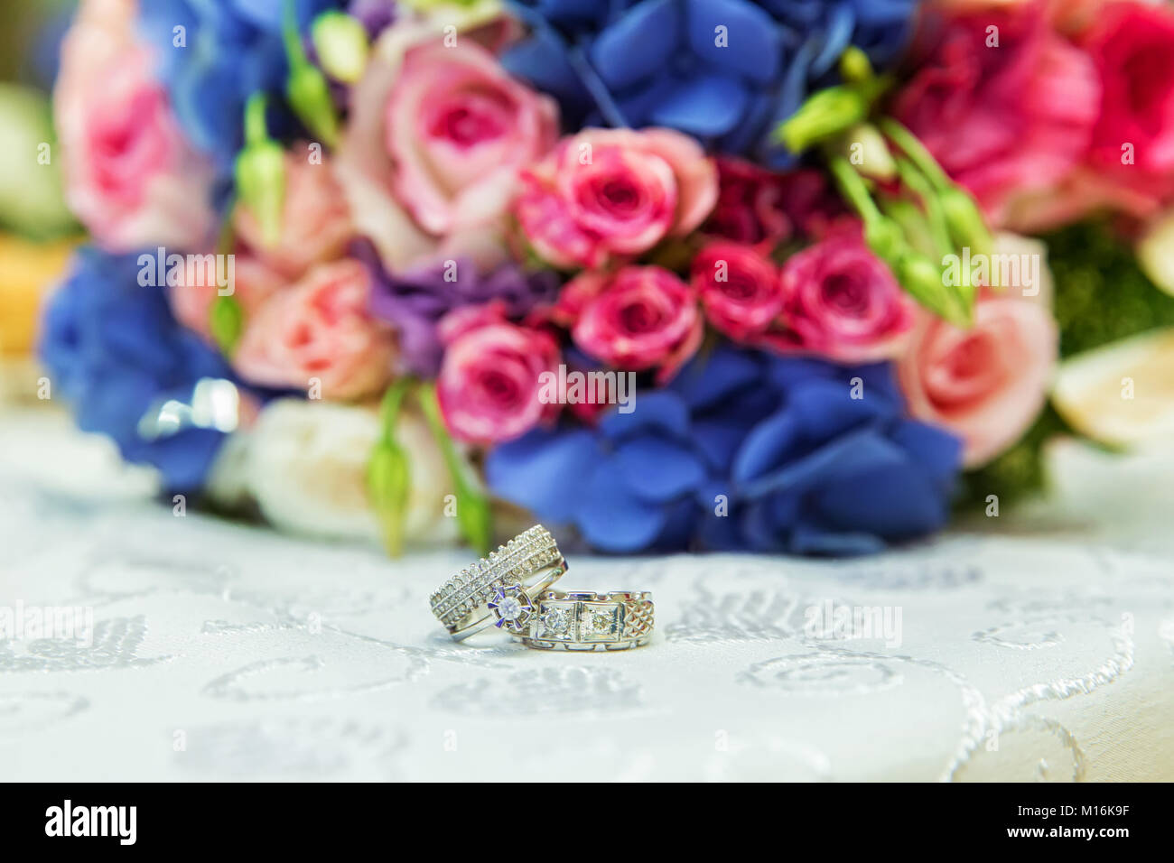 Mens wedding rings stock photos mens wedding rings stock images mens and bridal rings are on the background of a multi colored wedding bouquet izmirmasajfo