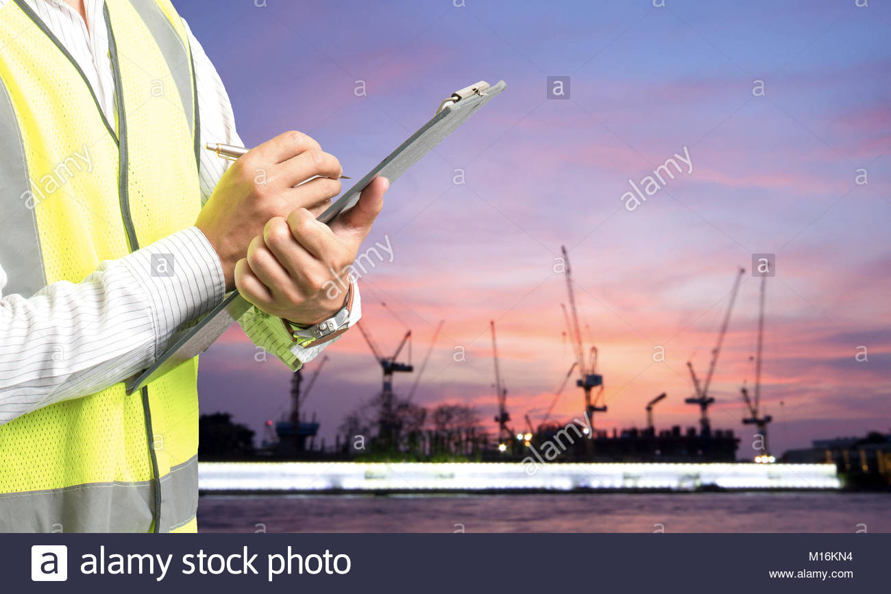 Portrait of young engineer taking notes - Stock Image
