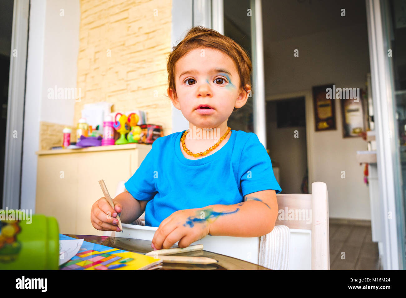 Mischievous baby bluc color markers innocent face painted child - Stock Image