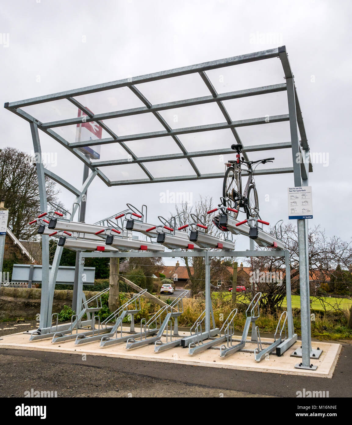 Single bicycle parked in new stacked bicycle parking stand, Drem train station, East Lothian, Scotland, UK - Stock Image
