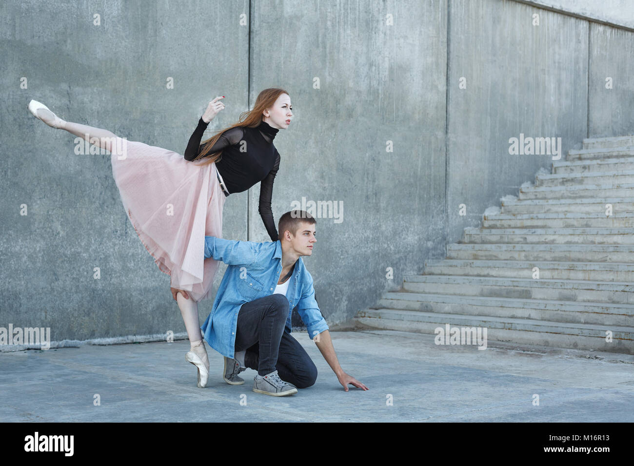 Slender ballerina dances with a modern dancer. Dating lovers. Performance in the streets of the city. Stock Photo