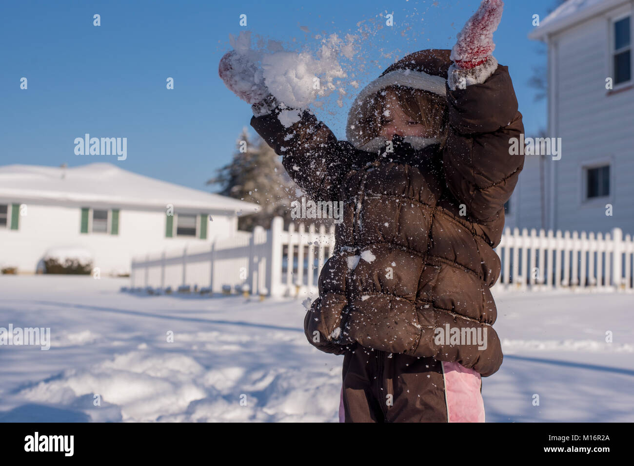 A 3-year old child throws snow up in the air on winter day in the United States. - Stock Image
