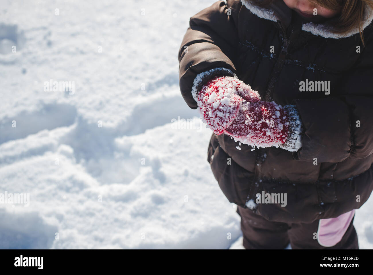 A 3-year old child wearing winter clothes, winter mittens, plays in the snow on a sunny winter day in the United - Stock Image