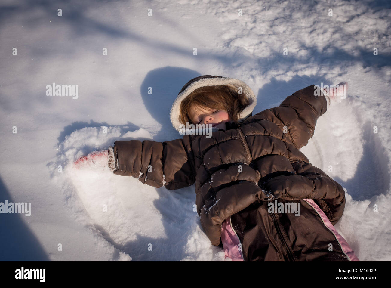 A three-year old girl makes a snow angel in the snow in northeast United States. - Stock Image
