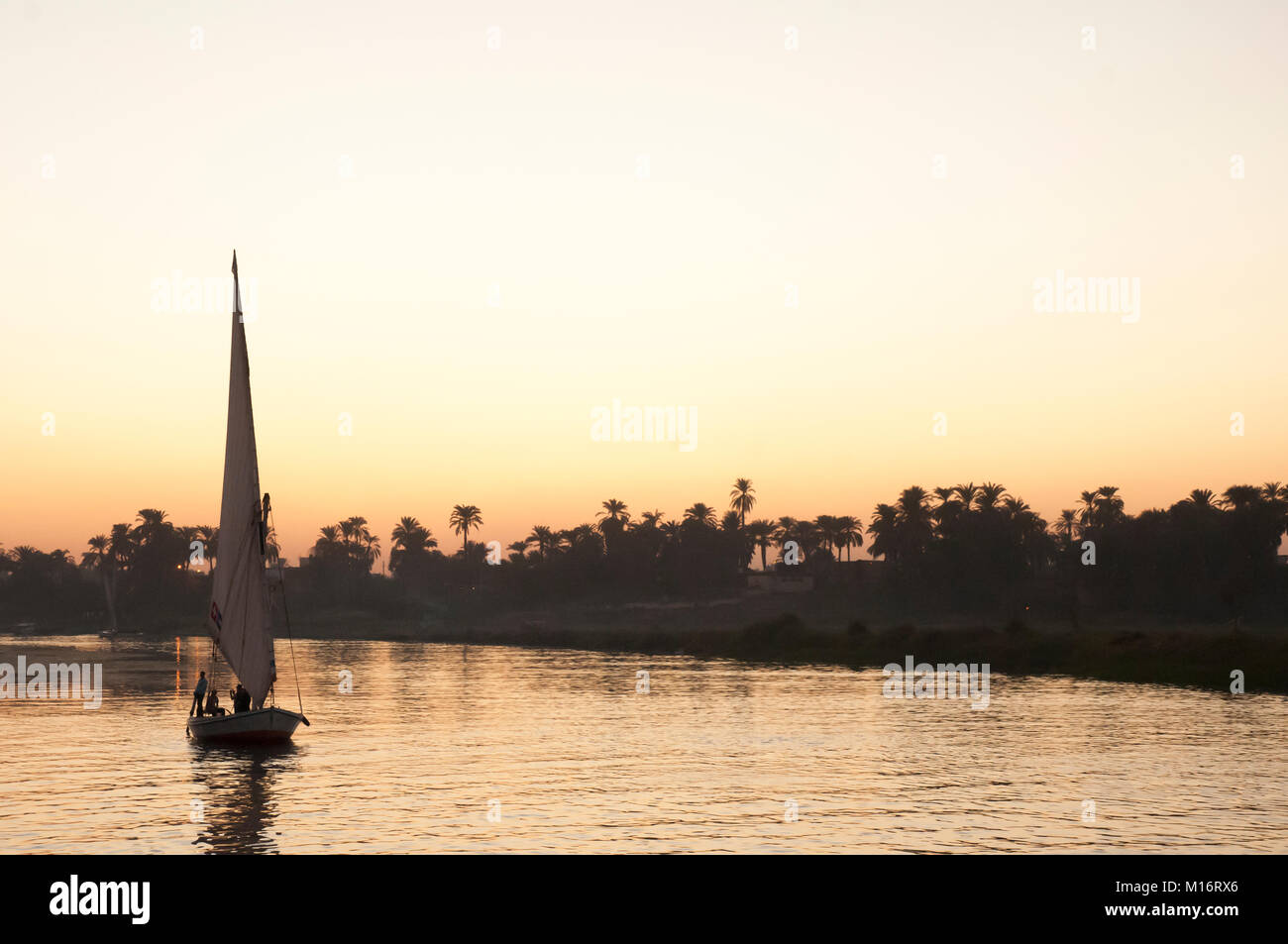 Traditional felucca ketch sailing on the Nile at sunset, Luxor, Egypt - Stock Image