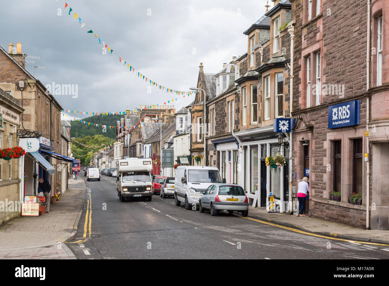 Comrie village - campervan driving through the Perthshire village of Comrie, Scotland, UK - Stock Image