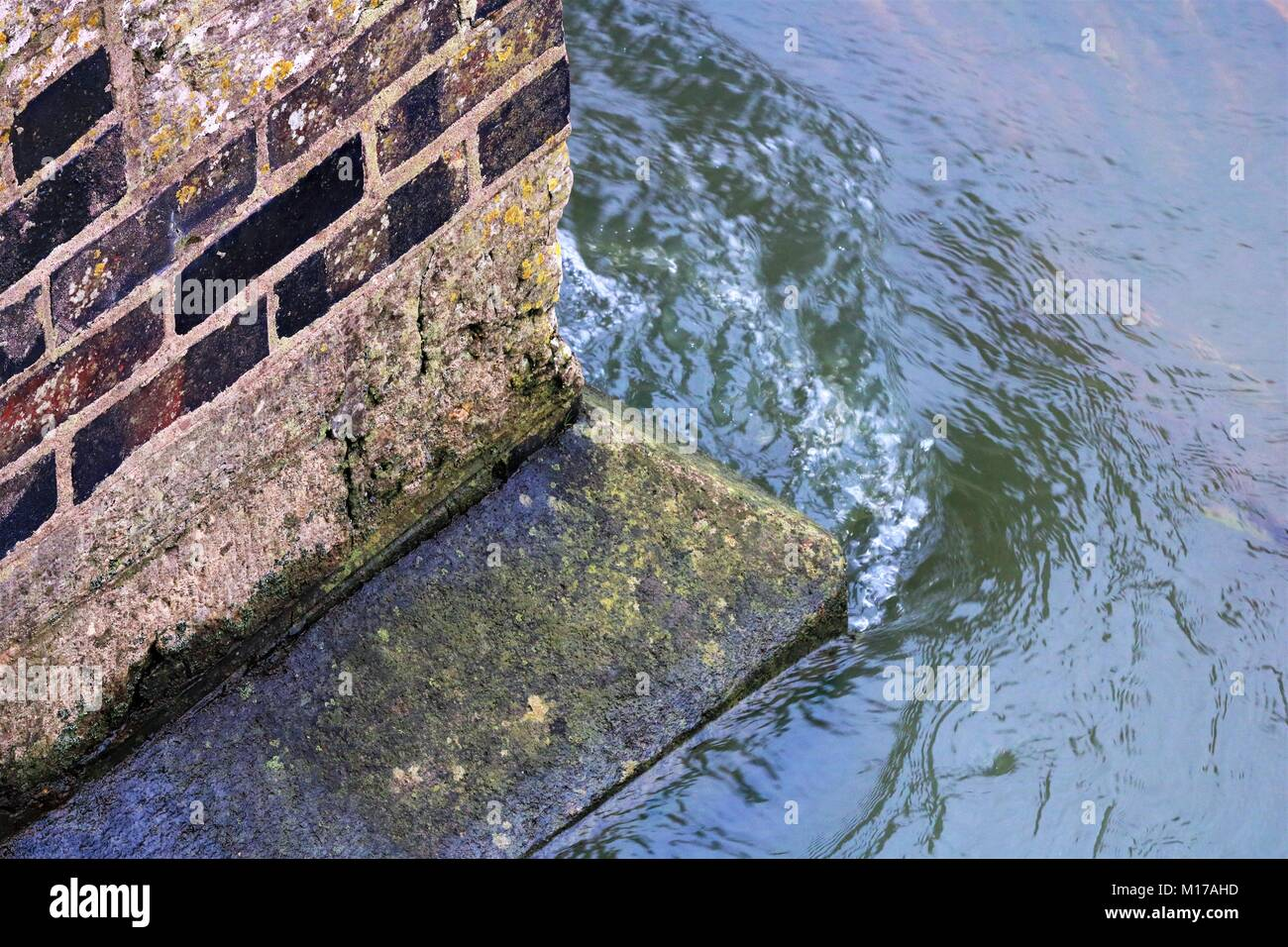 Angled view of flowing water hitting corner of bridge pillar resulting in ripples and bubbles in water - Stock Image