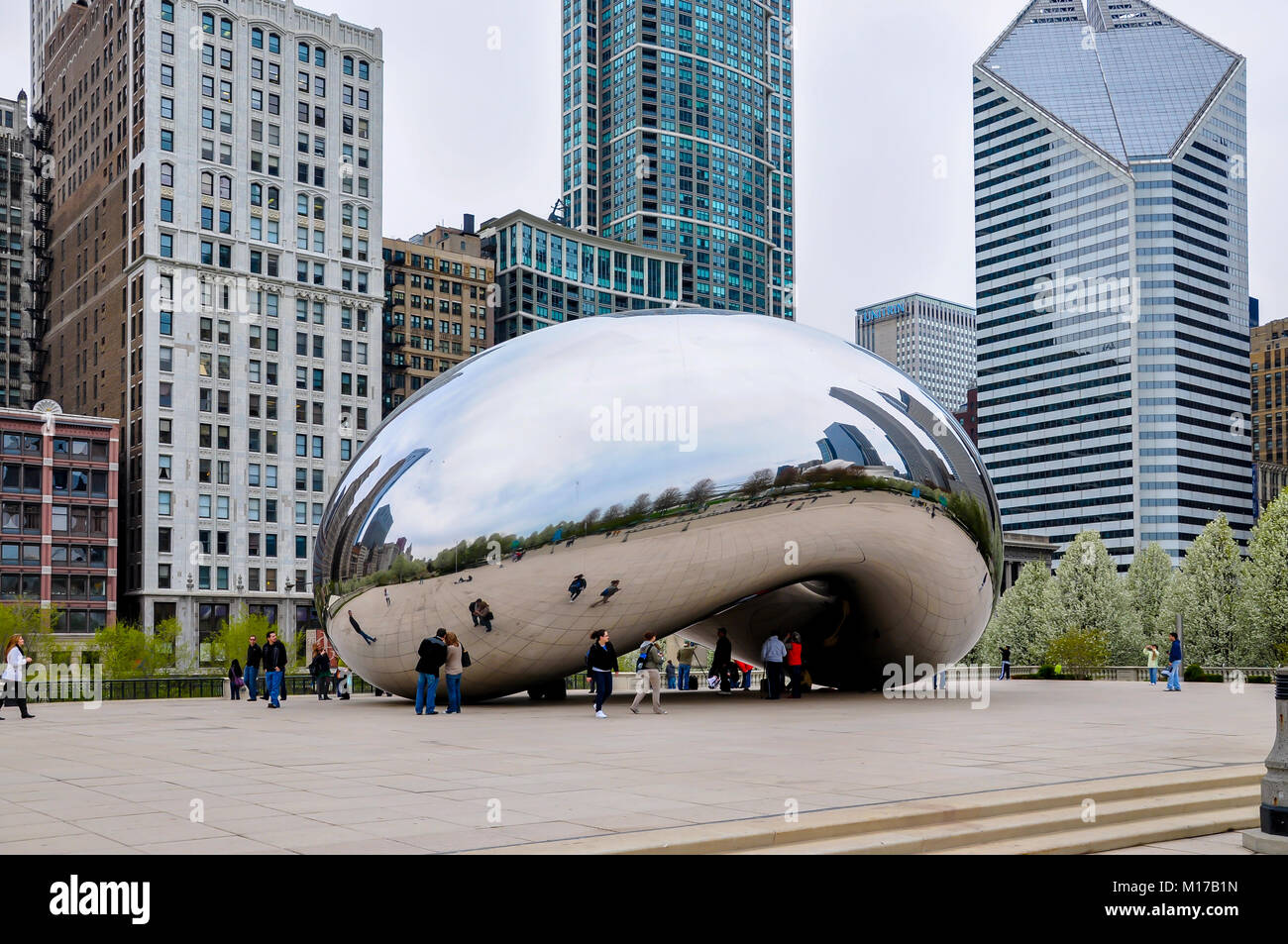Chicago, IL - MAY 5, 2011 - Cloud Gate (The Bean) Sculpture in Millennium Park with tourists and view of Chicago's - Stock Image