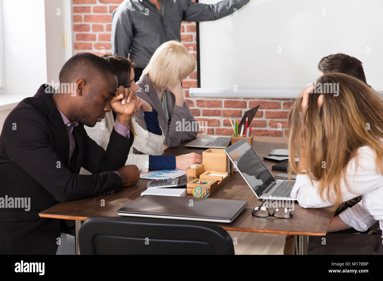 Diverse Tired Young Businesspeople Bored During Meeting In Office - Stock Image