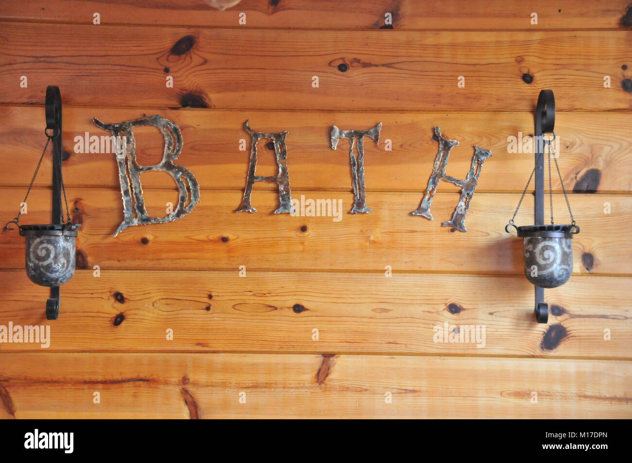 Distressed metal letters spelling out the word 'BATH' mounted on a knotty pine background. - Stock Image