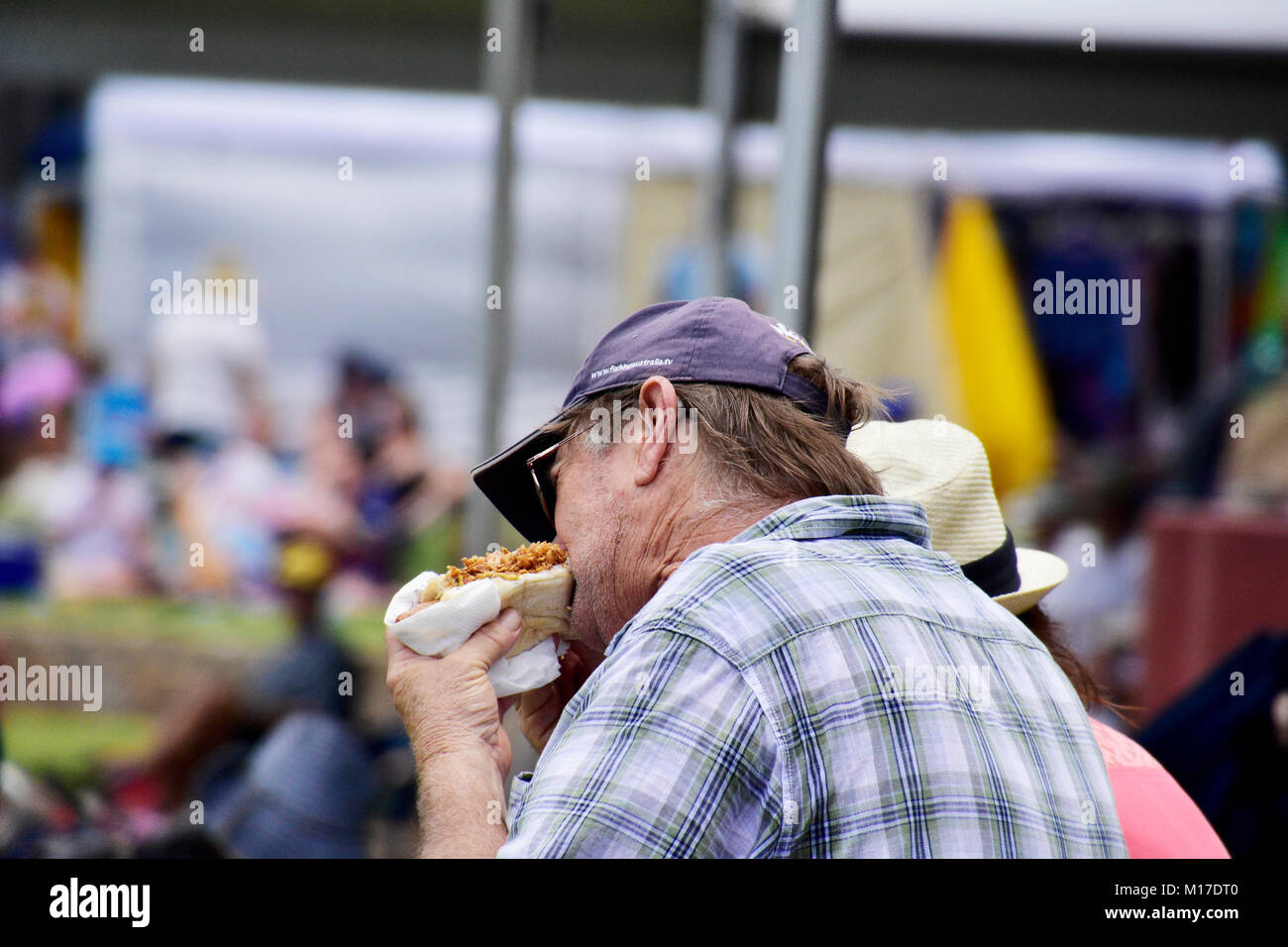 MATURE MAN EATING A HOT DOG - Stock Image