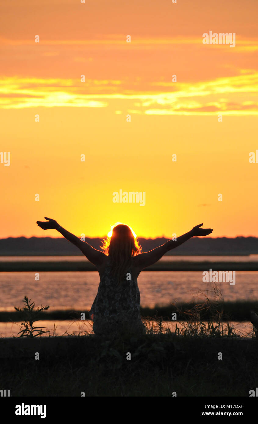 Woman enjoying a beautiful end of the day with open arms. - Stock Image
