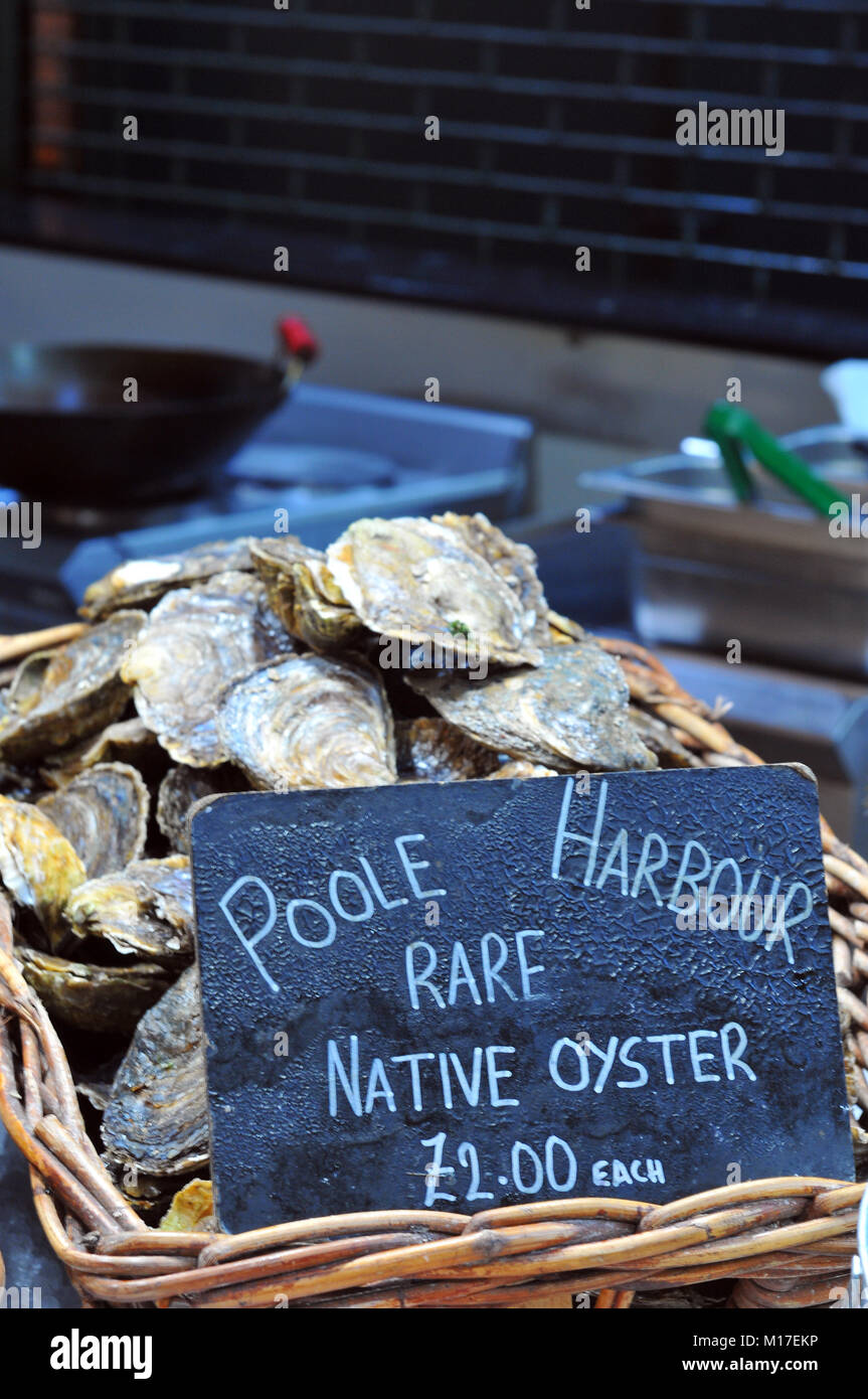 Poole harbour oysters caught by local shellfish fishermen and for sale on a stall at a fishmongers at5 borough market - Stock Image