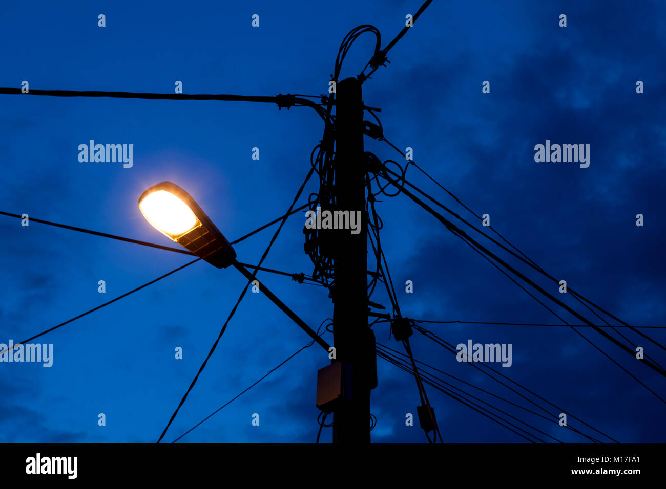 Overhead rural electricity power lines and telephone lines on a pole in a rural village in the U.K. - Stock Image