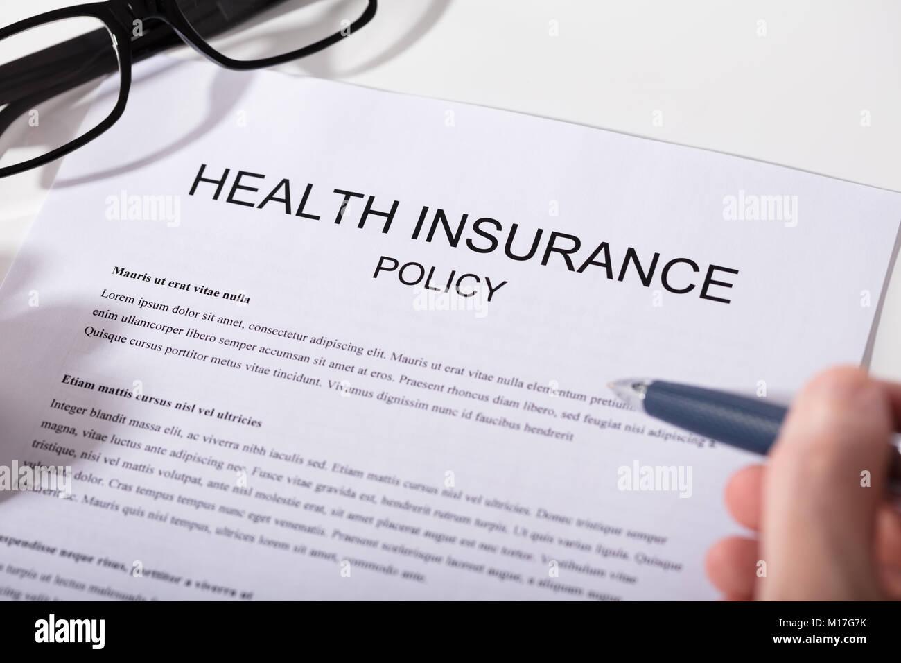 Close-up Of A Person's Hand Holding Pen Over Health Insurance Policy Form - Stock Image