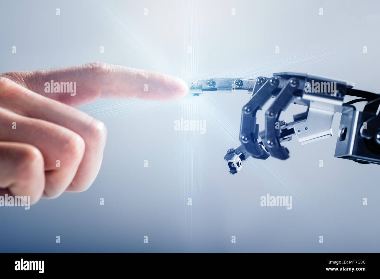 Close-up Of Businessperson's Finger Touching Robotic Finger On Blue Background - Stock Image