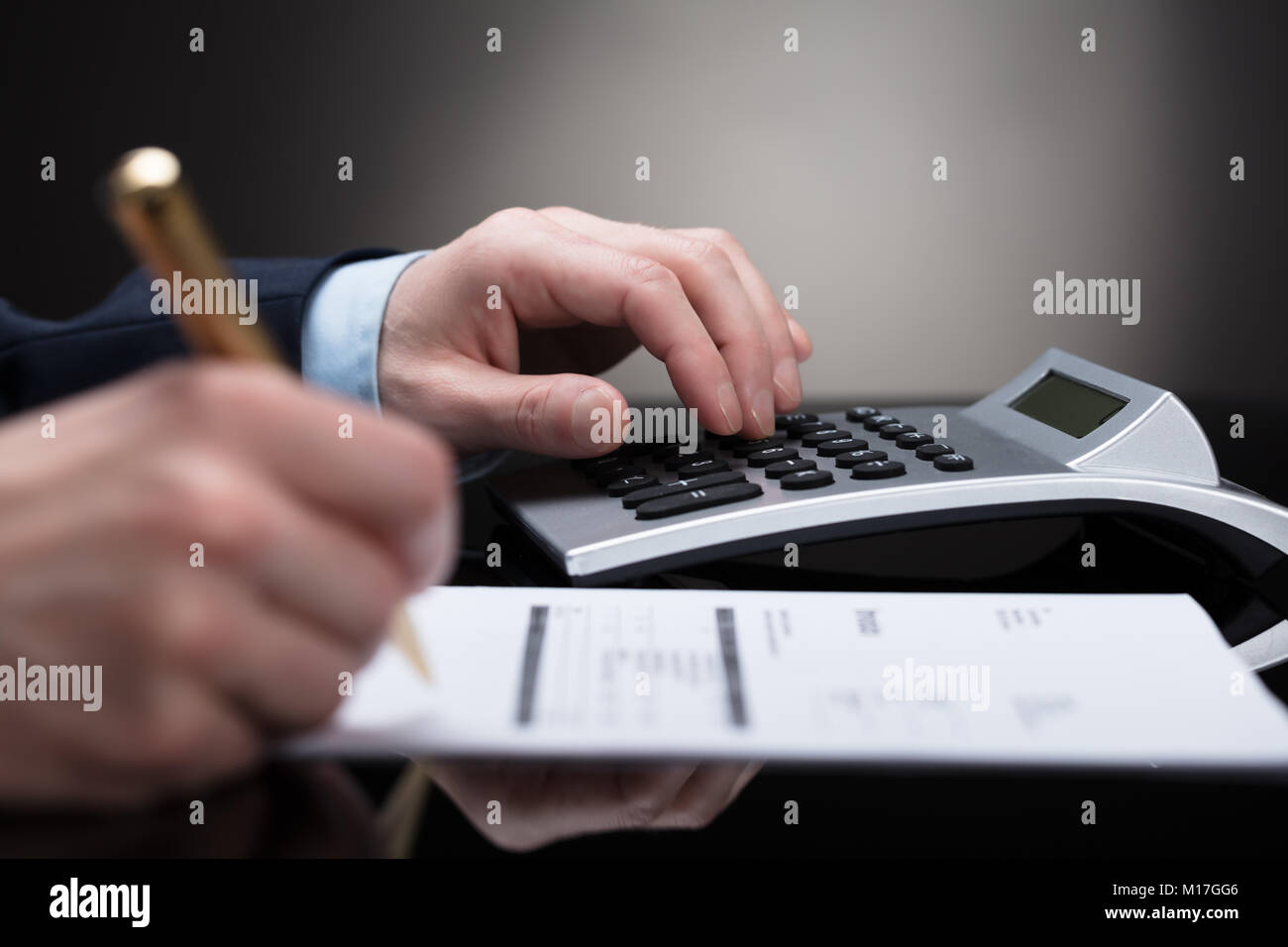 Businessperson Checking Invoice With Receipts On Desk - Stock Image
