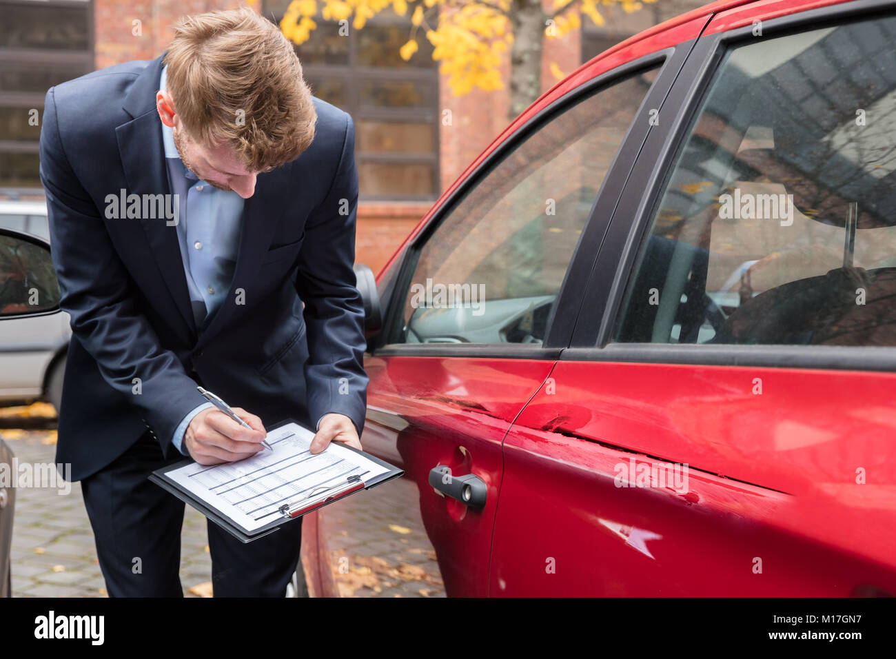 Insurance Agent Writing On Clipboard While Examining Car After Accident - Stock Image