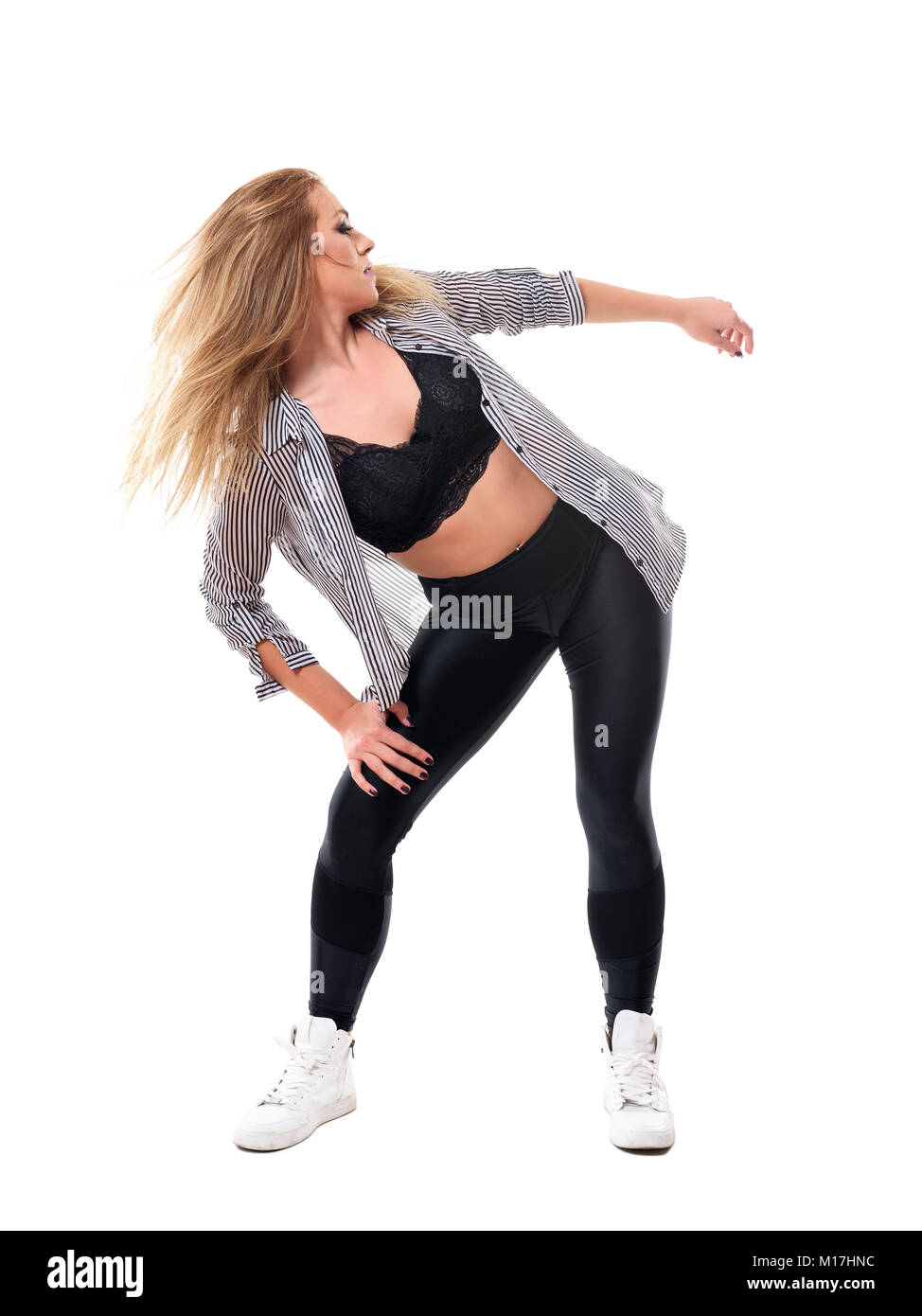 Young energetic woman banding and dancing in choreography with flowing hair toss. Full body length portrait isolated - Stock Image