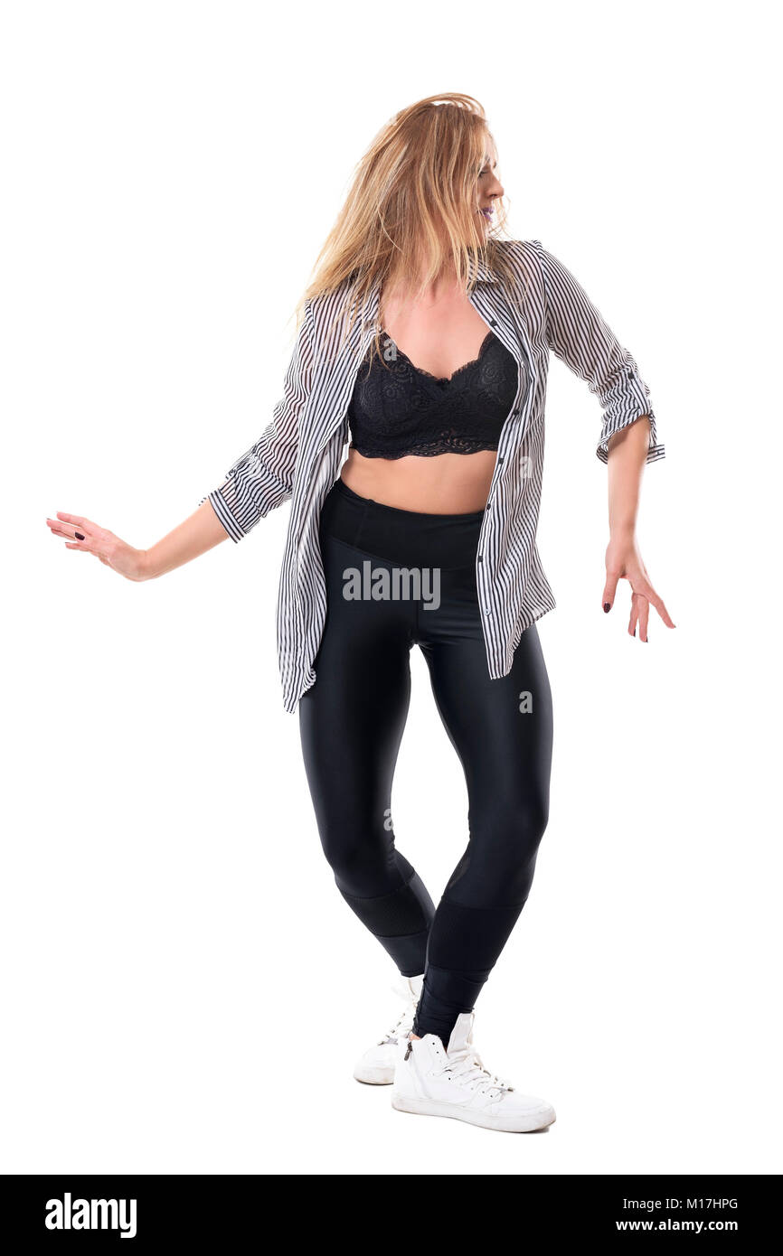 Passionate woman dancing in the music rhythm with tousled hair looking away. Full body length portrait isolated - Stock Image
