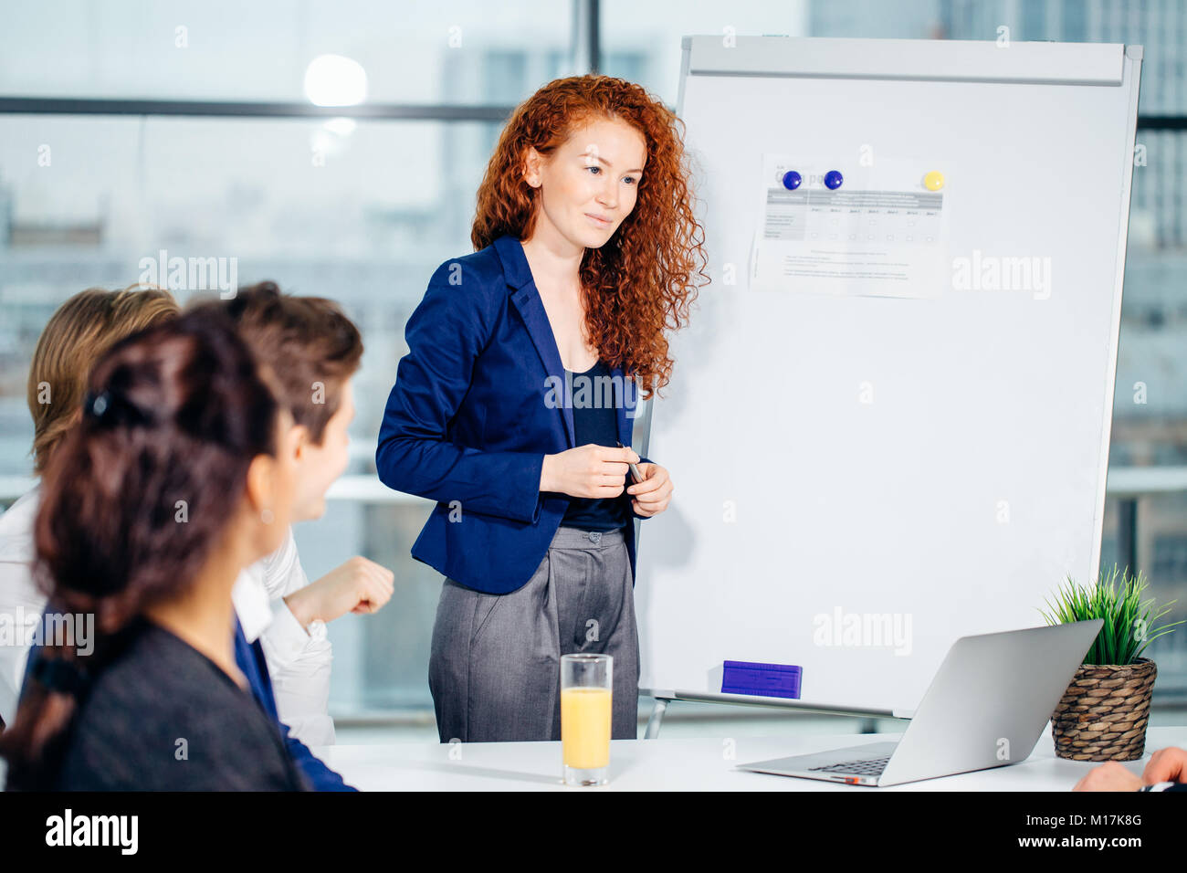 Business woman giving presentation to colleagues in office - Stock Image