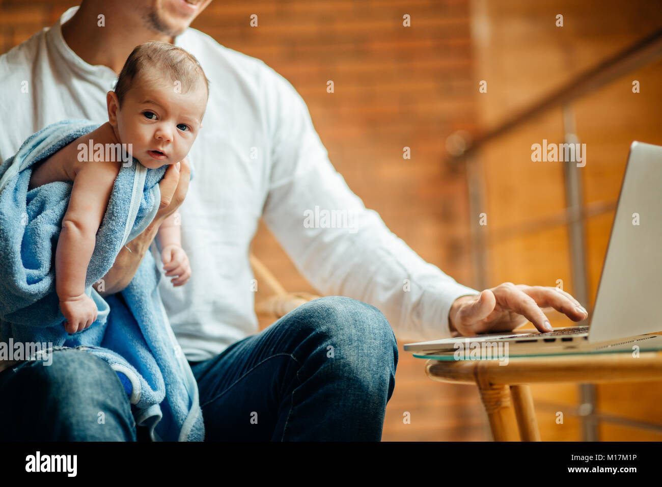 man working at desk at home with laptop, holding cute babys, looking at screen Stock Photo