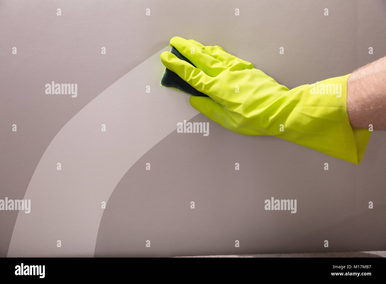 Close Up Of A Personu0027s Hand Wearing Gloves Cleaning Sofa With Sponge