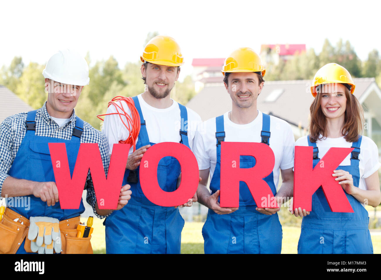 Group of workmen with word work outdoors - Stock Image