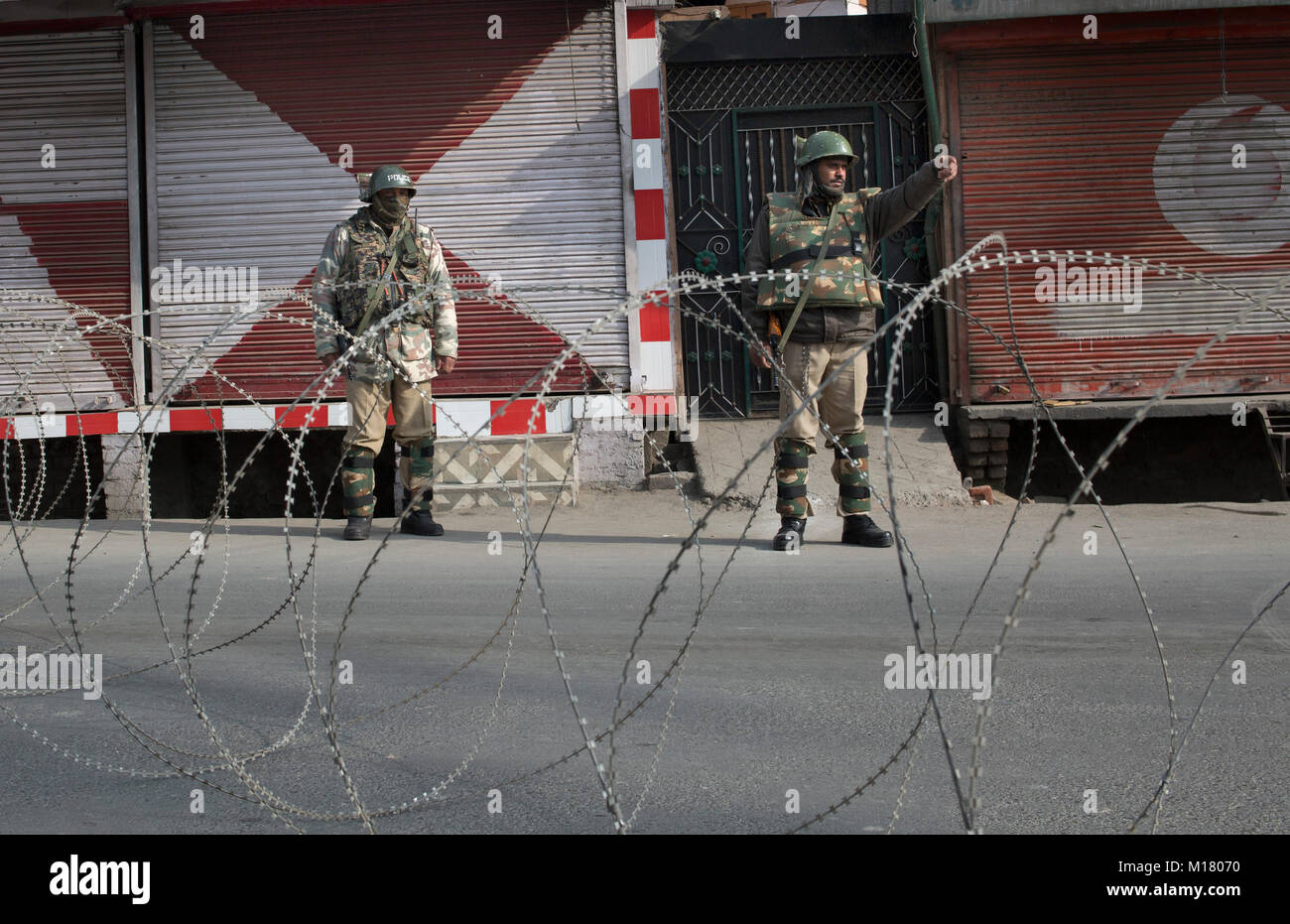 Srinagar, Indian-controlled Kashmir. 28th Jan, 2018. Indian paramilitary troopers stand guard near a barbed wire - Stock Image