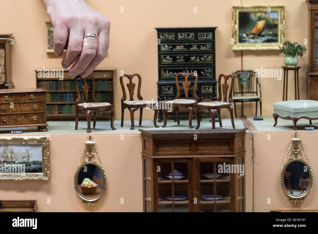 An Exhibitor Arranges Minature Furniture For Sale At