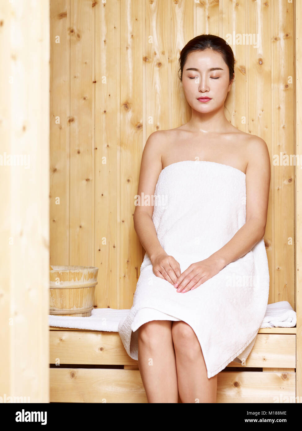 Beautiful Young Asian Woman Wrapped In White Towel Sitting