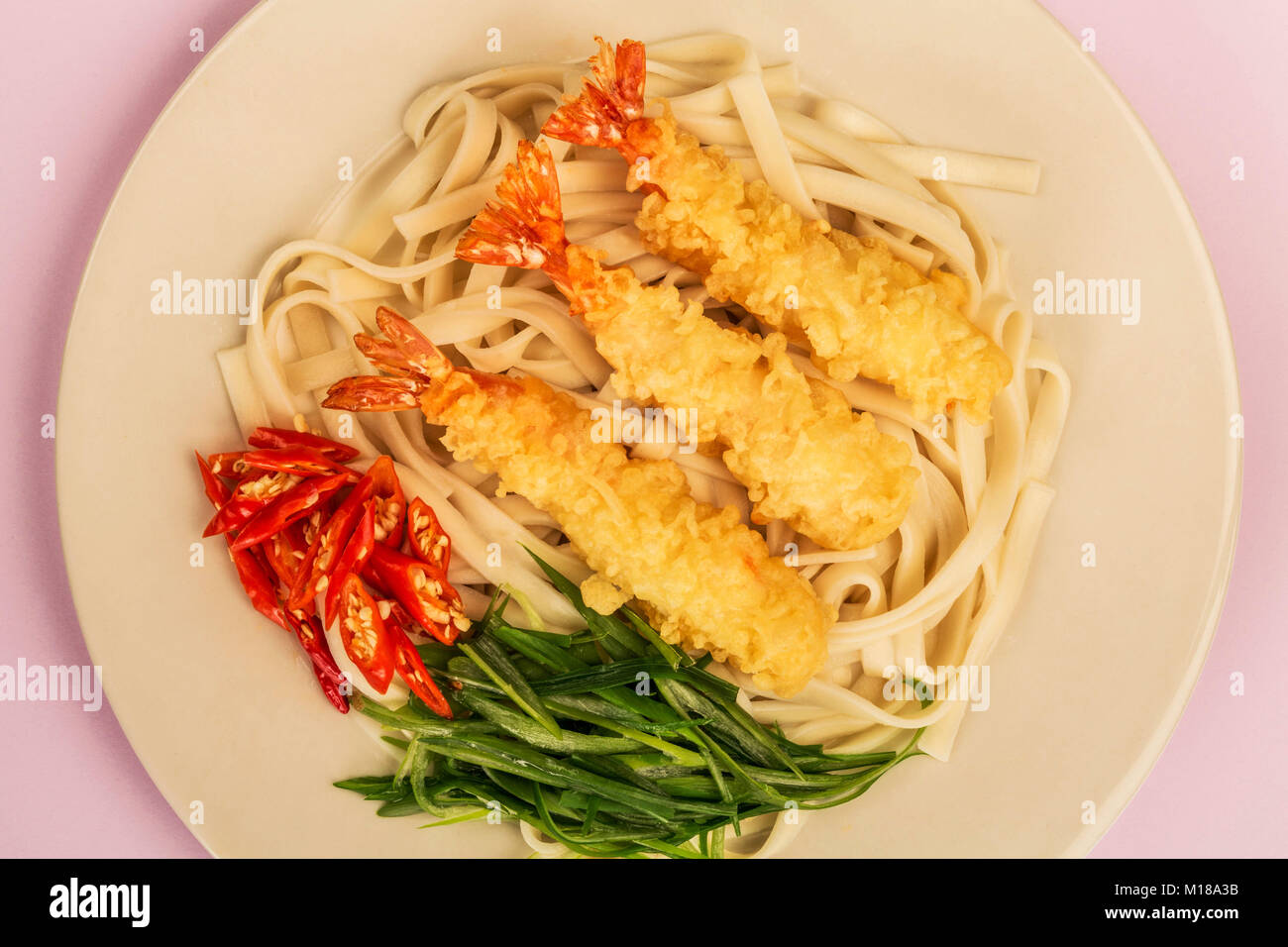 Japanese Style Tempura Prawns With Udon Noodles Chilli and Spring Onions Against A Lilac Background Stock Photo