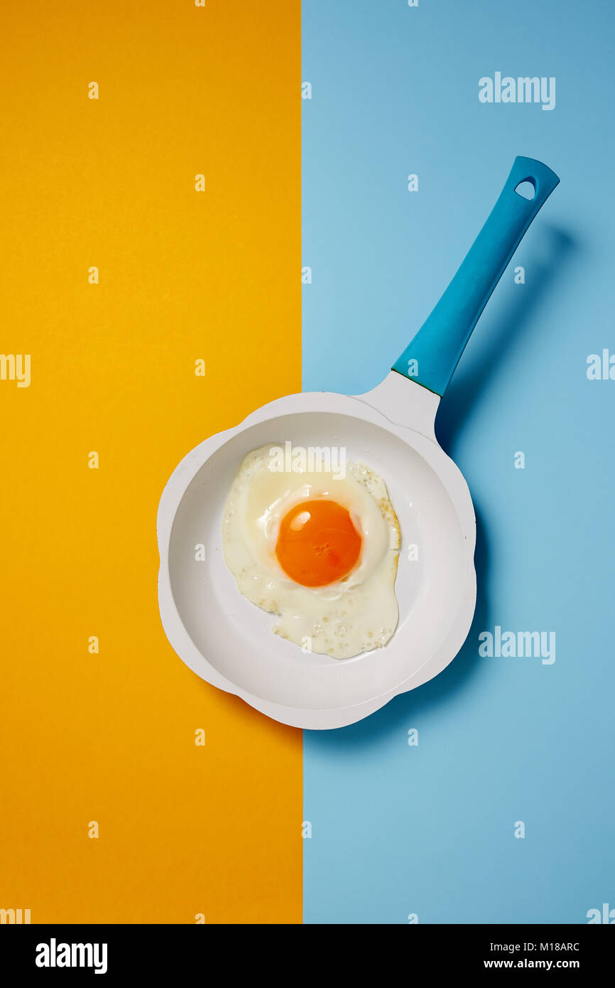 Fried egg in frying pan on colored background - Stock Image