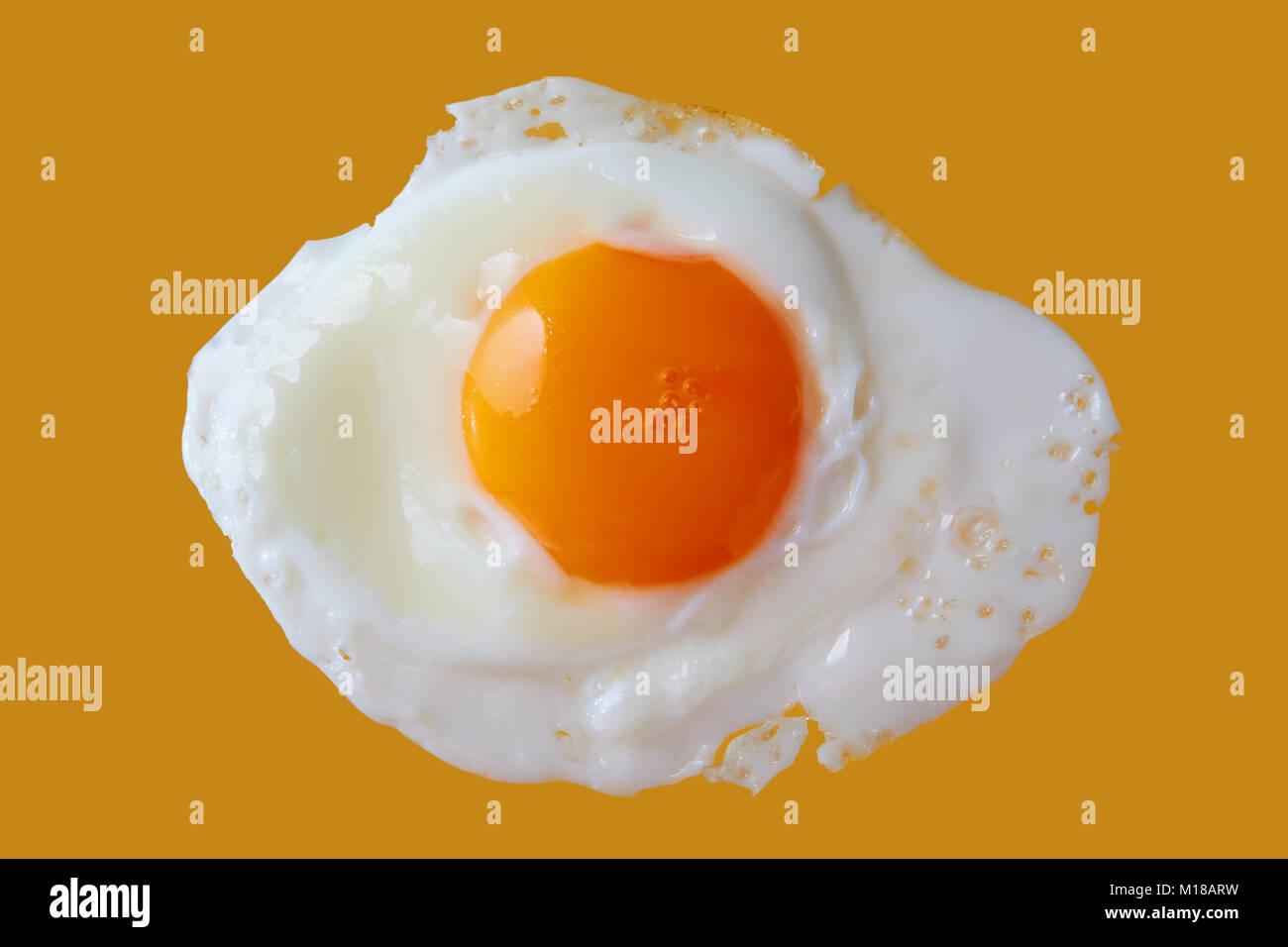 Fried egg on yellow background, close up - Stock Image