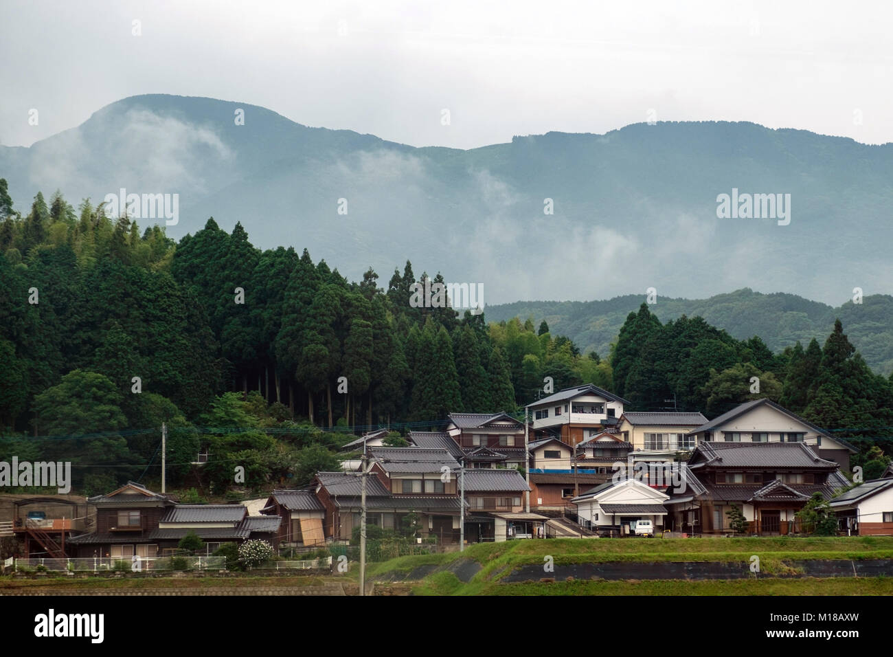 View of houses crowded together in rural Japan with misty mountains and tress in the background and rice fields - Stock Image