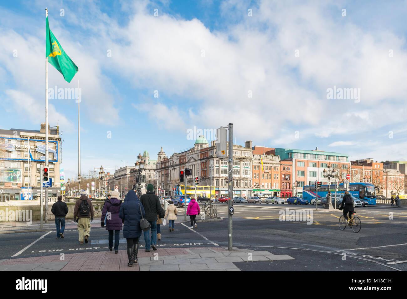 pedestrians crossing the road at O'Connell Bridge, Dublin facing towards O'Connell Street, Dublin, Ireland, - Stock Image