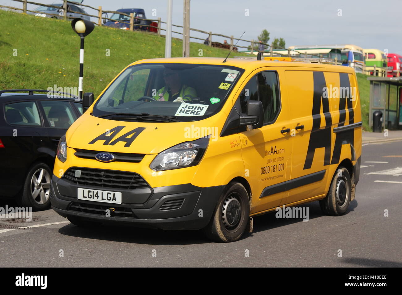A SUNNY NEARSIDE VIEW OF AN AA AUTOMOBILE ASSOCIATION YELLOW FORD TRANSIT PATROL VAN ON A BUSY TOWN CENTRE ROAD - Stock Image