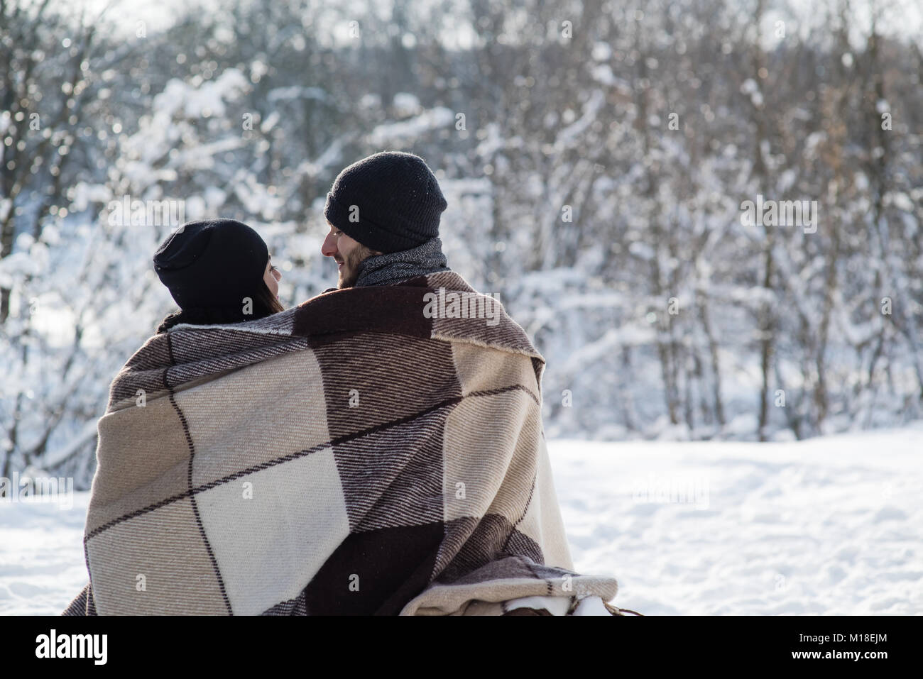 Boy and girl in black hats and plaid sitting on the snow background. Man and woman face each other. - Stock Image