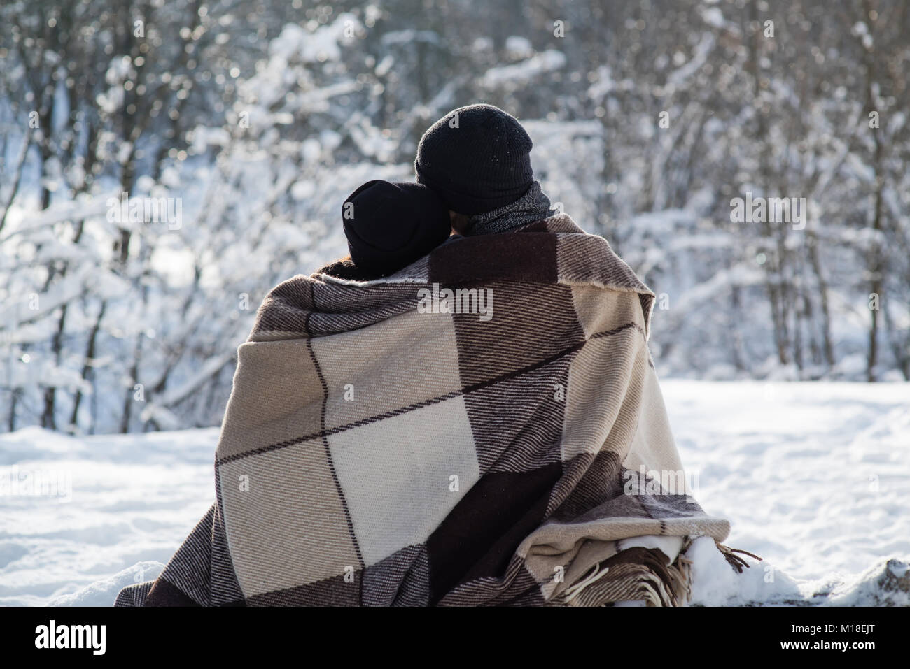 Boy and girl in black hats and plaid sitting on the snow background - Stock Image