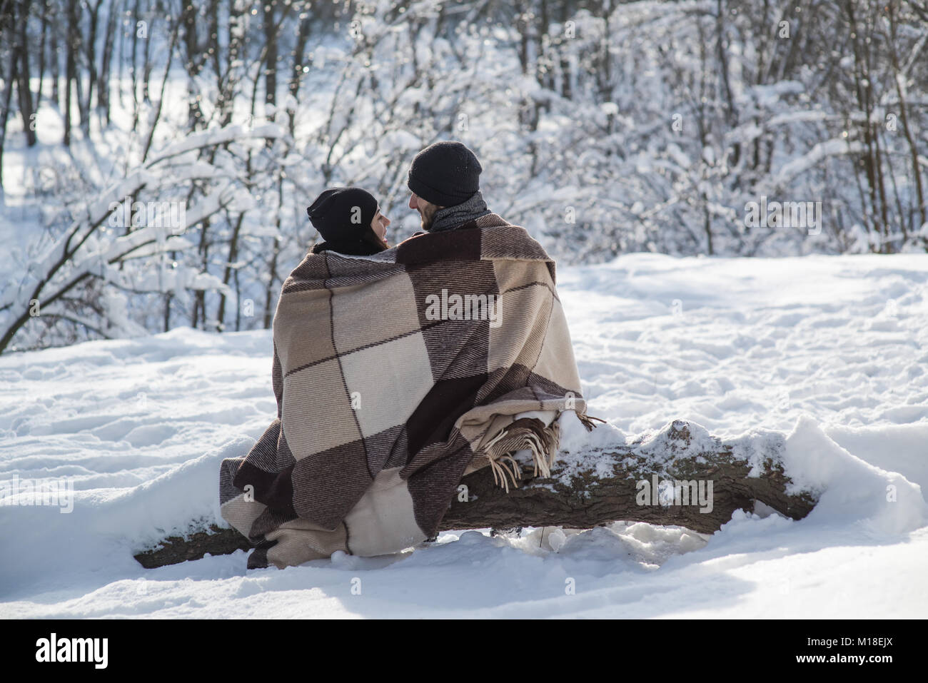 Boy and girl in black hats and plaid sitting on the snow background. Couple sitting on a log. - Stock Image